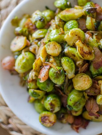 Brussels sprouts with bacon and onions in a bowl.