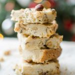 Hazelnut shortbread bars with a chai glaze stacked on top of each other on a plate with a Christmas tree in the background