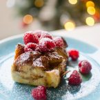 A slice of eggnog French toast with raspberries and powdered sugar with a Christmas tree in the background.