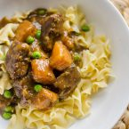 Beef and butternut squash stew on egg noodles in a white bowl.