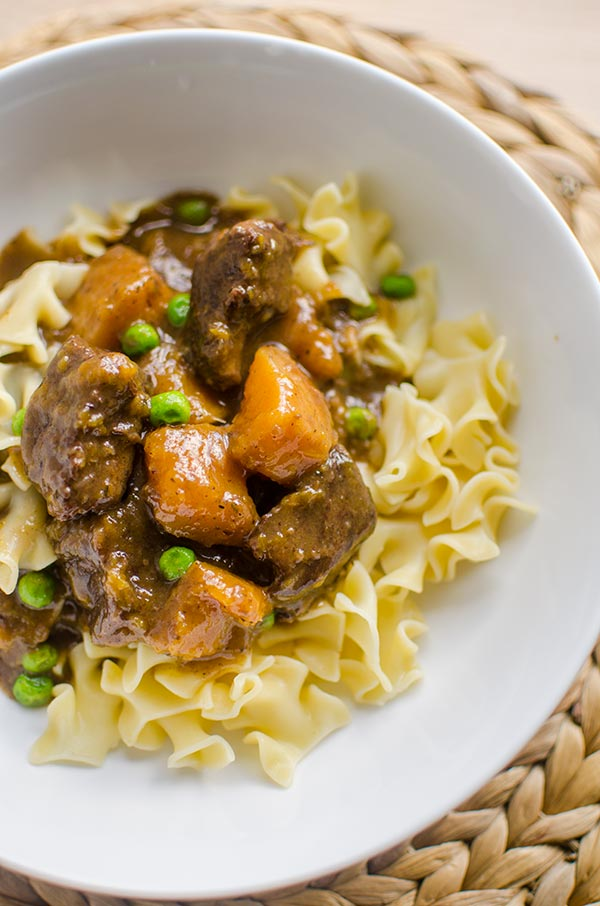 Make the perfect melt in your mouth and tender beef and butternut squash stew, made with stewing beef, butternut squash and peas. | livinglou.com