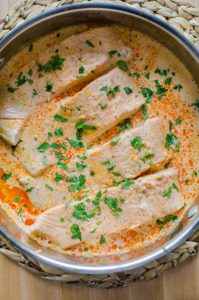 Whole pot of four salmon fillets in their poaching liquid (curried coconut milk) sprinkled with fresh cilantro.
