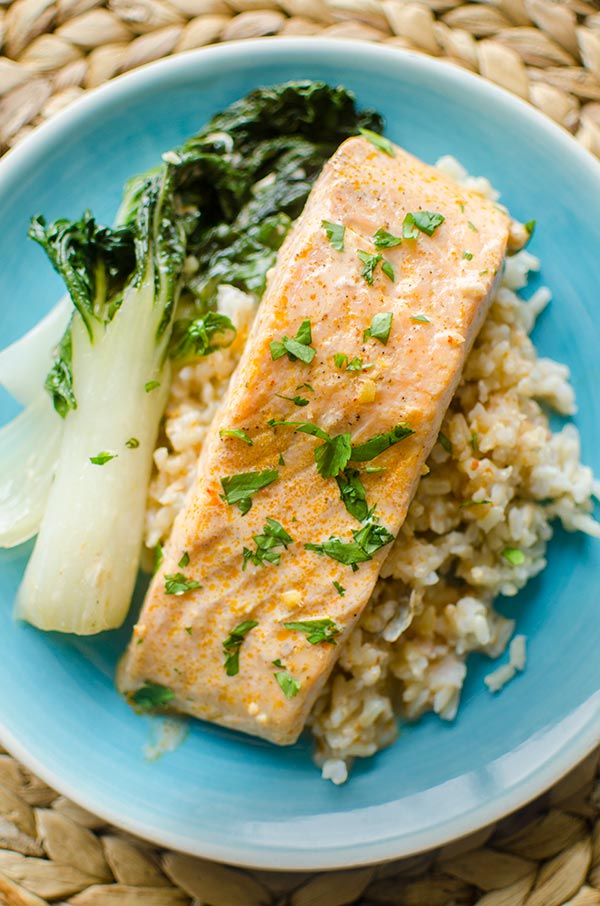 Plate of poached salmon with a curried coconut milk broth with brown rice, bok choy and fresh cilantro.