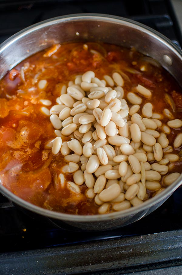 Braised chicken thighs with tomatoes and white beans is a comforting one pot meal made with onions, tomatoes, garlic, white beans  for a savoury delicious dinner.  | livinglou.com