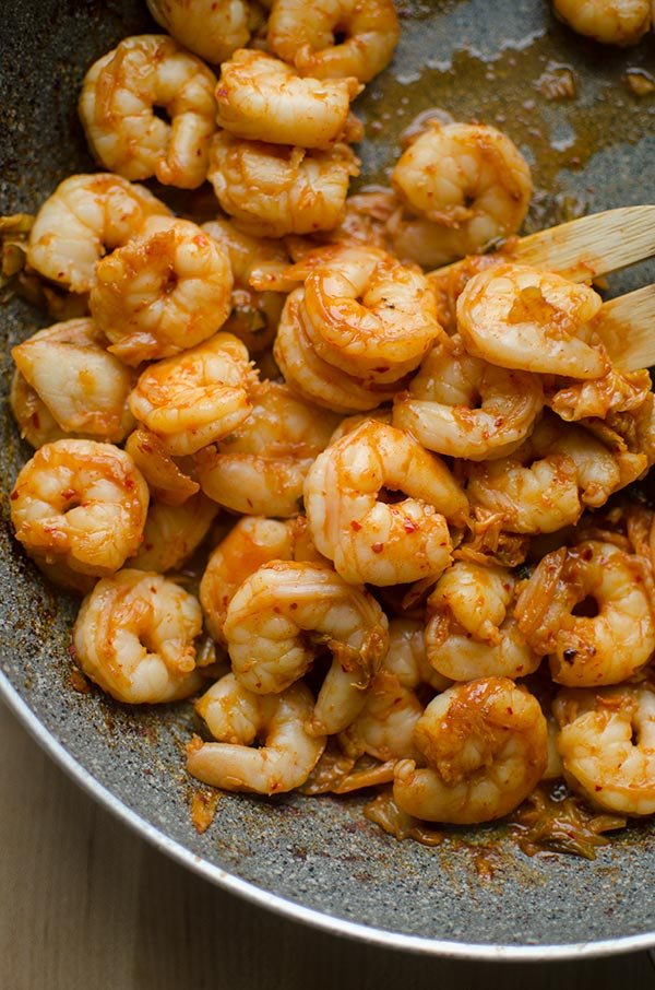 Shrimp marinated in gochujang, fish sauce, garlic and soy sauce stir frying in a skillet.