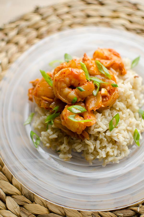 Shrimp and kimchi stir fry over a bed of brown rice with green onions.
