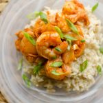 Closeup of shrimp and kimchi stir fry over brown rice with green onions.