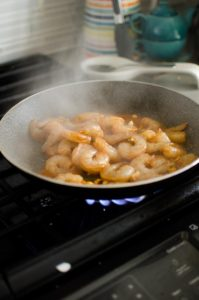 Raw marinated shrimp stir frying in a hot pan.
