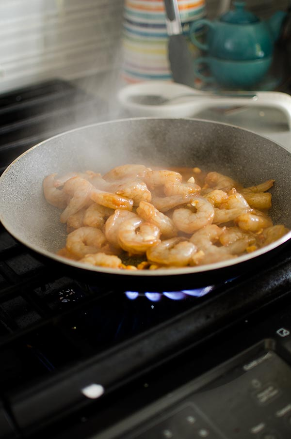 Raw marinated shrimp stir frying in a hot pan.