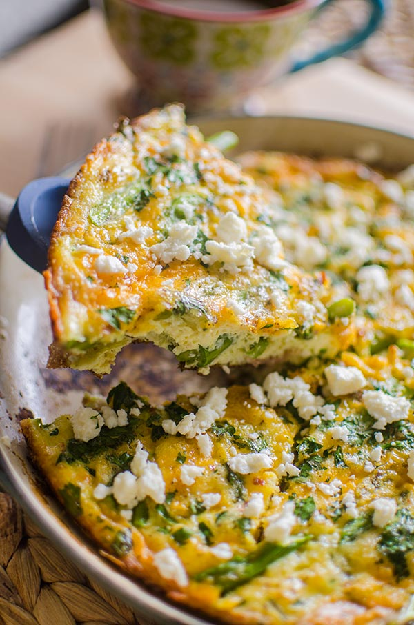 A slice of bacon and asparagus frittata topped with feta.