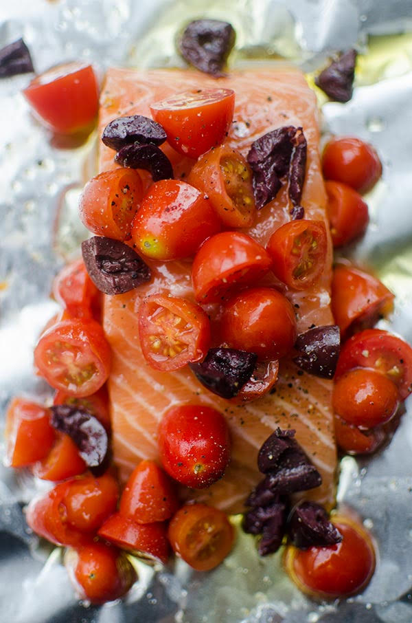 Raw salmon fillet in foil packet with cherry tomatoes and kalamata olives.