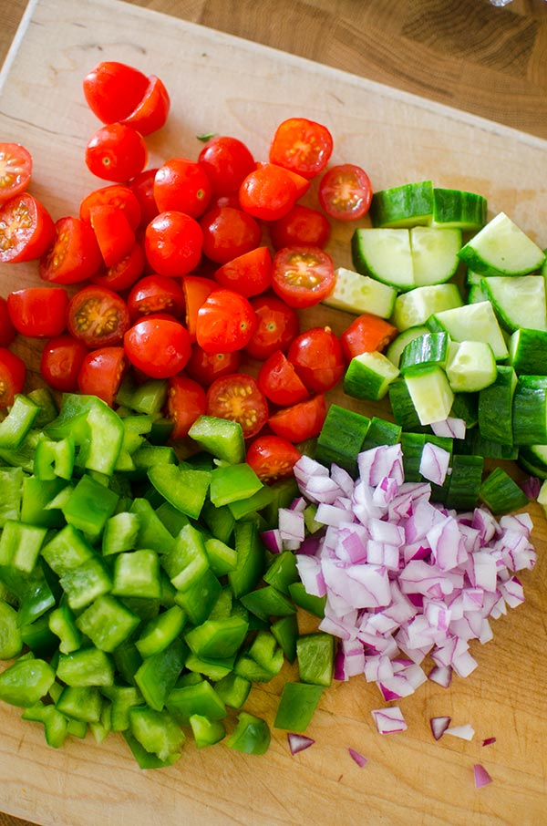 Ingredients (cherry tomatoes, cucumber, green pepper and red onion) prepped on a cutting board.