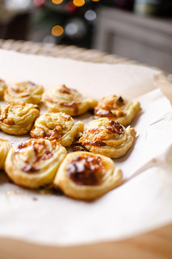 Side angle of puff pastry brie bites with Christmas tree in the background
