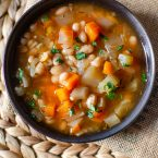 slow cooker navy bean soup in a black bowl with parsley on top