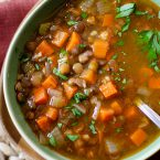 closeup of lentil soup in a green bowl with parsley sprinkled on top