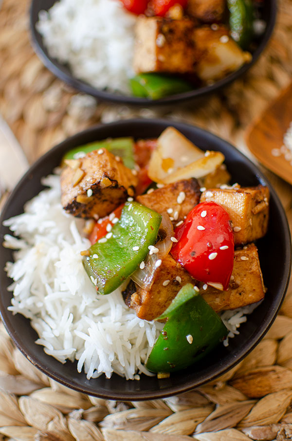 Closeup of tofu stir fry in a black bowl.