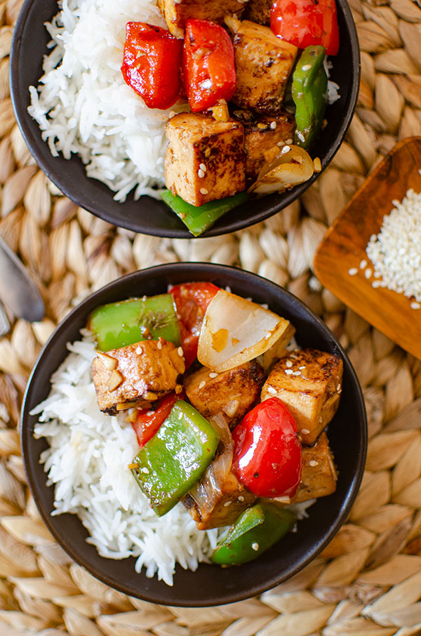 Two servings of tofu bell pepper stir fry with rice in a black bowl.