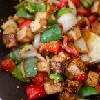 Tofu bell pepper stir fry in a wok.