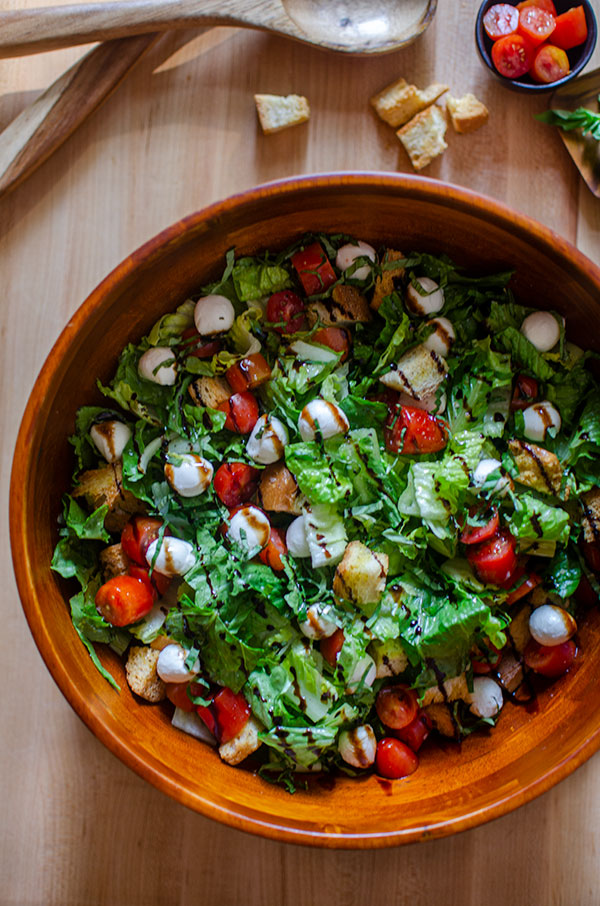 A bowl of bruschetta salad with balsamic drizzle on a wooden board.