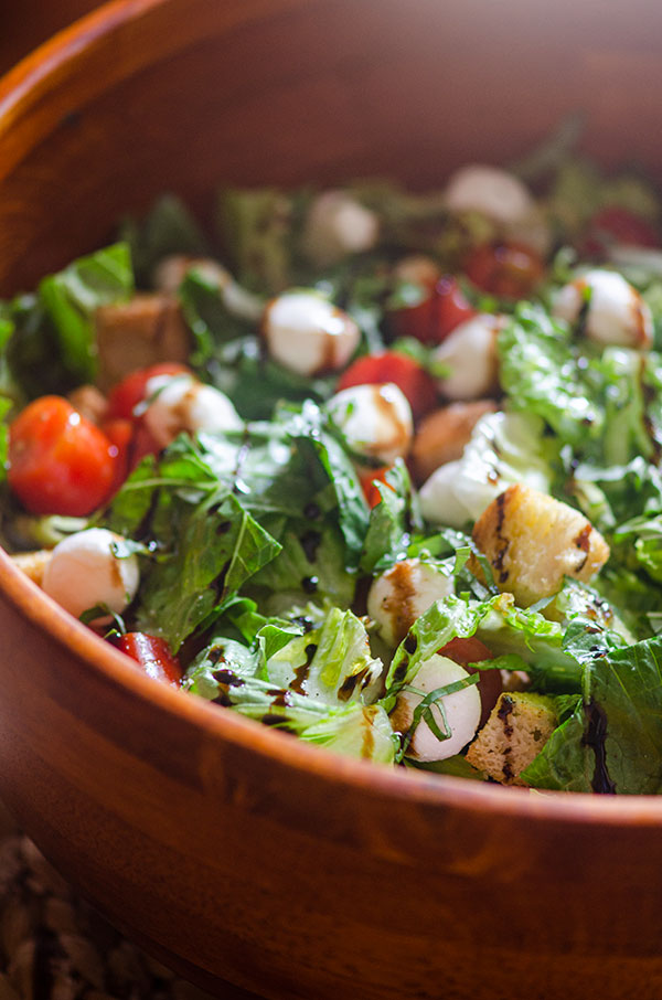 Macro closeup of bruschetta salad in a wooden salad bowl.