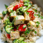 Closeup of tofu stir fry on top of brown rice in a white bowl