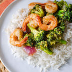 Shrimp and broccoli stir fry over rice on a white plate with an orange napkin