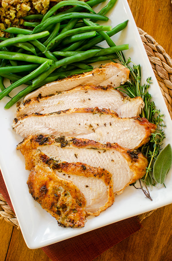 Slices of turkey breast on a platter with fresh herbs, green beans and stuffing.
