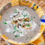 Cream of mushroom soup in an orange bowl with cream and satueed mushrooms on top.