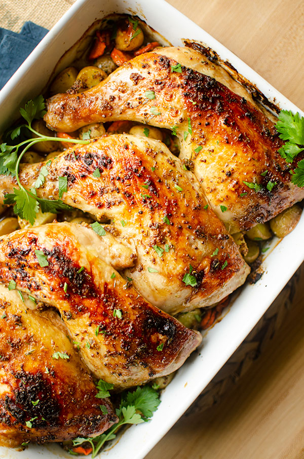 Closeup of cooked chicken quarters in a baking dish