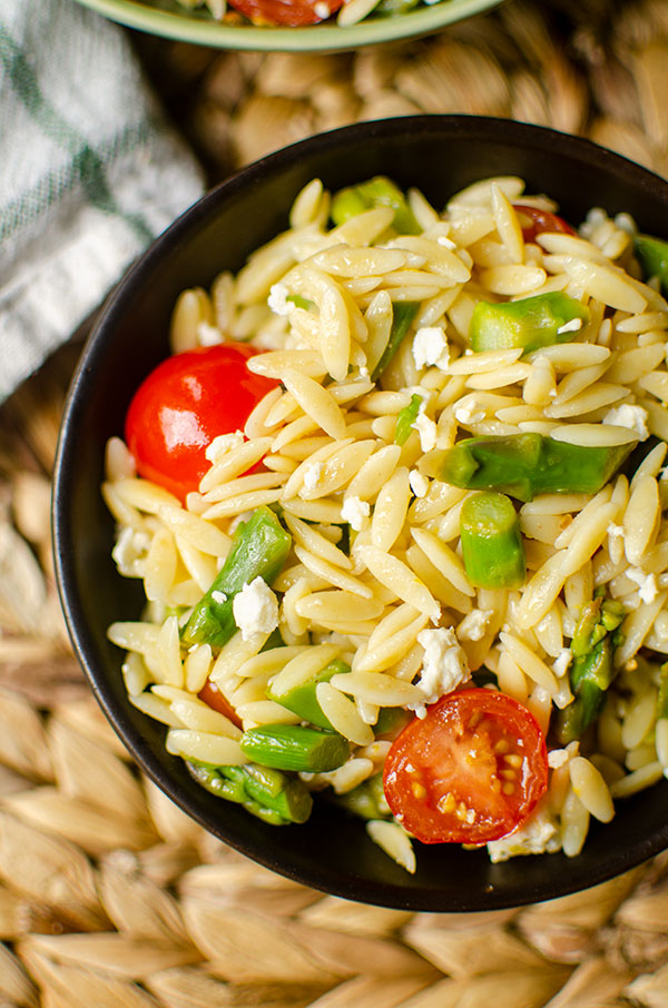 Closeup of orzo in a black bowl.