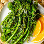 Roasted broccoli rabe on a plate with sliced oranges
