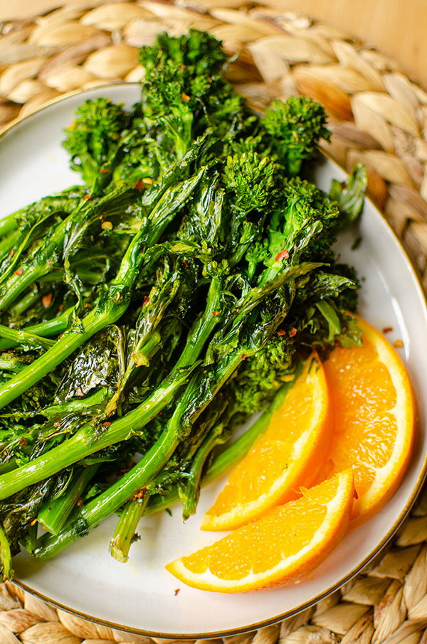 Closeup of roasted borrocoli rabe on a plate with slices of orange