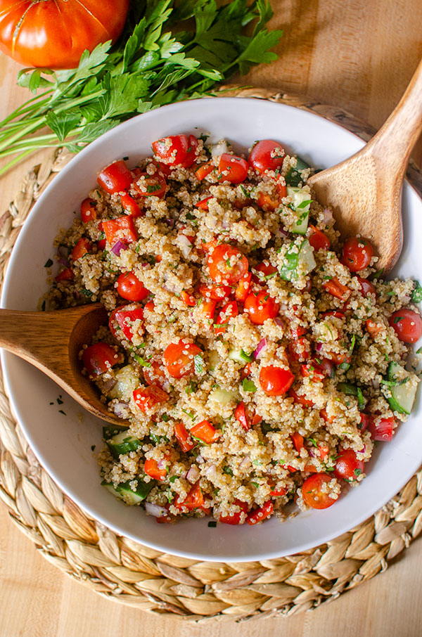 A big bowl of quinoa salad on a placemart with parsley and tomato.